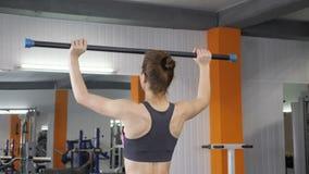 做在她的与杠铃酒吧的肩膀前面的年轻美丽的运动的女孩锻炼在健身房 60 fps后部视图 股票录像