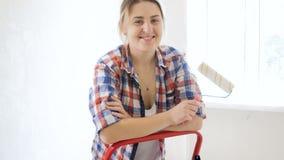 做在她的公寓的整修和看在照相机的愉快的微笑的年轻女人录影画象  影视素材