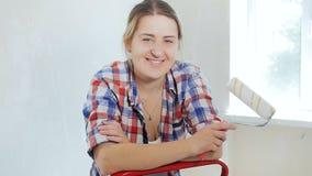做在她的公寓的整修和看在照相机的愉快的微笑的年轻女人录影画象  股票录像