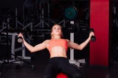 做在她的胸肌的性感的女孩锻炼 与哑铃的健身在健身房 好逗人喜爱的女性 免版税库存图片