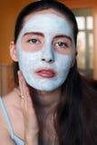 做在她的面孔的妇女化妆面具 免版税库存图片