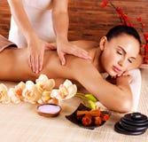 做在妇女身体的男按摩师按摩温泉沙龙的 免版税库存照片