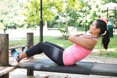 做在室外锻炼公园的妇女仰卧起坐 免版税图库摄影