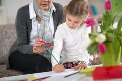 做在家庭作业的女孩在祖母帮助下 库存图片