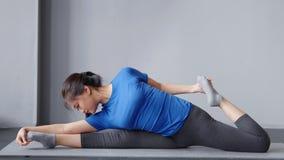 做在家舒展的全景体操亚裔年轻女人在席子或瑜伽演播室 影视素材