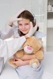 做在小女孩的医生膏药 免版税库存图片