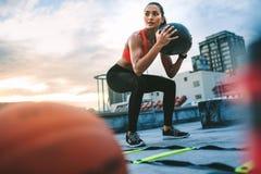 做在屋顶的健身妇女锻炼 免版税库存照片