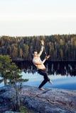 做在山的上面的中年人体育瑜伽,室外生活方式的人,训练的夏天狂放的自然 免版税库存图片