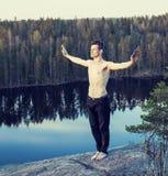 做在山的上面,生活的中年人体育瑜伽 免版税库存照片