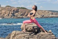做在岩石海岸线的年轻深色的妇女瑜伽 免版税库存图片