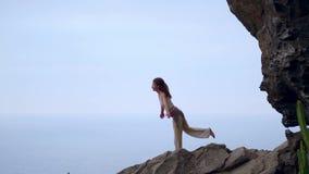 做在岩石海滨的少妇瑜伽在日落 一种健康生活方式的概念 和谐 人类本性 的treadled 影视素材