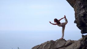 做在岩石海滨的少妇瑜伽在日落 一种健康生活方式的概念 和谐 人类本性 的treadled 股票视频
