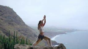 做在岩石海滨的少妇瑜伽在日落 一种健康生活方式的概念 和谐 人类本性 的treadled 股票录像