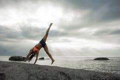 做在岩石的妇女手倒立在Bakovern海滩,开普敦的日落 免版税库存图片