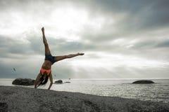 做在岩石的妇女手倒立在Bakovern海滩,开普敦的日落 图库摄影