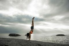 做在岩石的妇女手倒立在Bakovern海滩,开普敦的日落 免版税库存照片