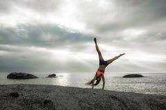 做在岩石的妇女手倒立在Bakovern海滩,开普敦的日落 库存图片