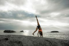做在岩石的妇女手倒立在Bakovern海滩,开普敦的日落 库存照片