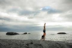 做在岩石的妇女手倒立在Bakovern海滩,开普敦的日落 免版税图库摄影