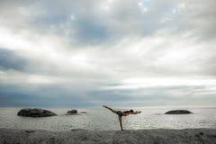 做在岩石的妇女瑜伽在Bakovern海滩,开普敦的日落 免版税图库摄影