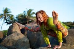 做在岩石的女孩瑜伽 库存照片