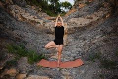 做在岩石的运动人瑜伽 库存照片