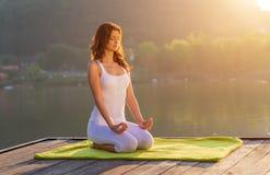 做在岸的妇女瑜伽-半图开会 免版税库存图片