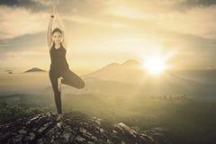 做在峭壁的俏丽的妇女瑜伽锻炼 库存图片