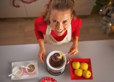 做在巧克力釉的愉快的年轻主妇苹果在厨房里 免版税库存照片