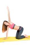 做在席子演播室射击的年轻美丽的妇女瑜伽 免版税库存图片