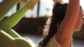 做在席子的一位可爱的女性教练员asanas在瑜伽演播室 股票录像
