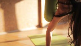 做在席子的一位女性个人教练员asanas在瑜伽演播室 影视素材