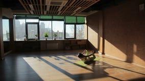 做在席子的一女性asanas在瑜伽演播室 股票录像
