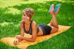 做在席子的女孩锻炼在绿草的公园 图库摄影