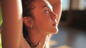 做在席子的女性个人教练员asanas在瑜伽集中 影视素材