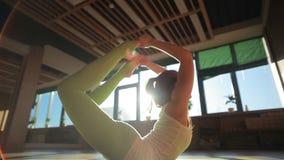 做在席子的女性个人教练员asanas在瑜伽集中 股票视频