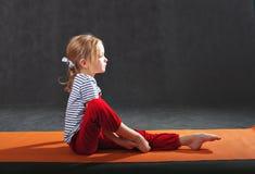 做在席子的小女孩锻炼瑜伽的 拉扯手 免版税图库摄影