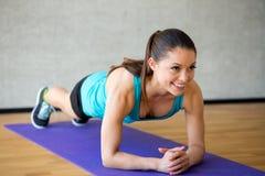 做在席子的微笑的妇女锻炼在健身房 图库摄影