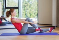做在席子的微笑的妇女锻炼在健身房 免版税库存照片