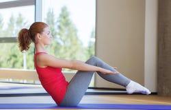 做在席子的微笑的妇女锻炼在健身房 库存照片