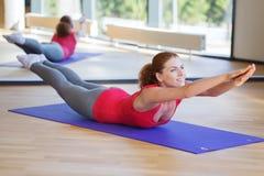 做在席子的微笑的妇女锻炼在健身房 库存图片