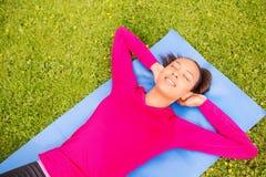 做在席子的微笑的妇女锻炼户外 图库摄影