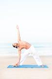 做在席子的运动人瑜伽在海滩 图库摄影