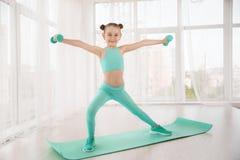 做在席子的运动服的小运动的女孩体操运动员锻炼室内 图库摄影