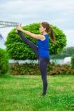 做在席子21的少妇瑜伽锻炼 免版税库存图片