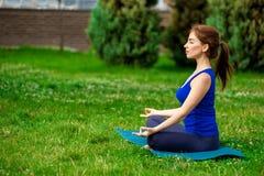 做在席子13的少妇瑜伽锻炼 免版税库存照片