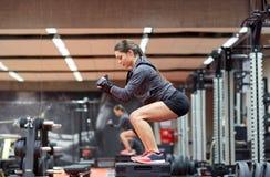 做在平台的妇女蹲坐在健身房 免版税库存图片