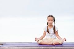 做在平台的孩子锻炼户外 健康生活方式 背景女孩查出的空白瑜伽 免版税库存照片