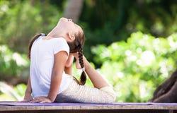 做在平台的孩子锻炼户外 健康生活方式 背景女孩查出的空白瑜伽 免版税库存图片