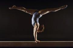 做在平衡木的体操运动员分裂手倒立 库存照片